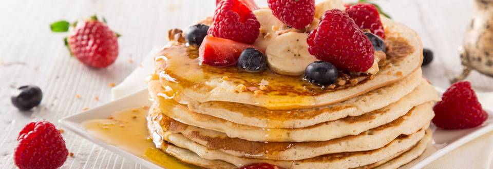 Pancakes con frutta fresca, burro d'arachidi, muesli, gelatina e sciroppo d'acero